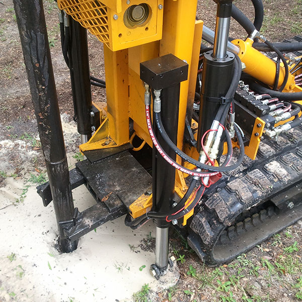 Drilling rig for compaction grounting with pipe clamp.